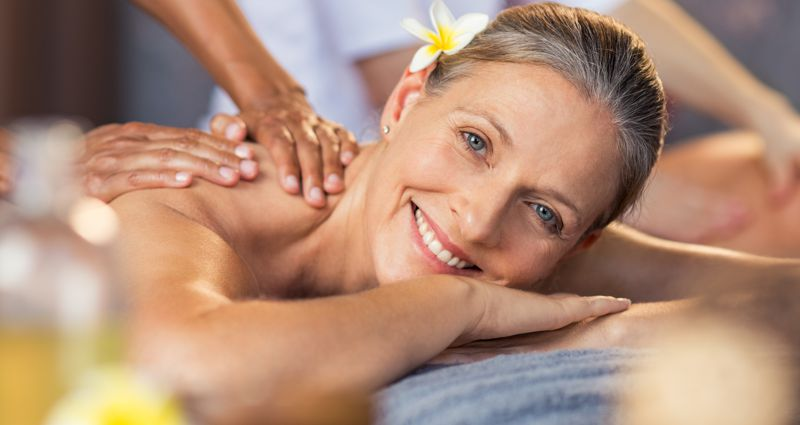 Happy senior woman getting oil massage on her back at spa center. Portrait of senior woman receiving back massage. Closeup face of smiling mature woman relaxing on massage table and looking at camera.
